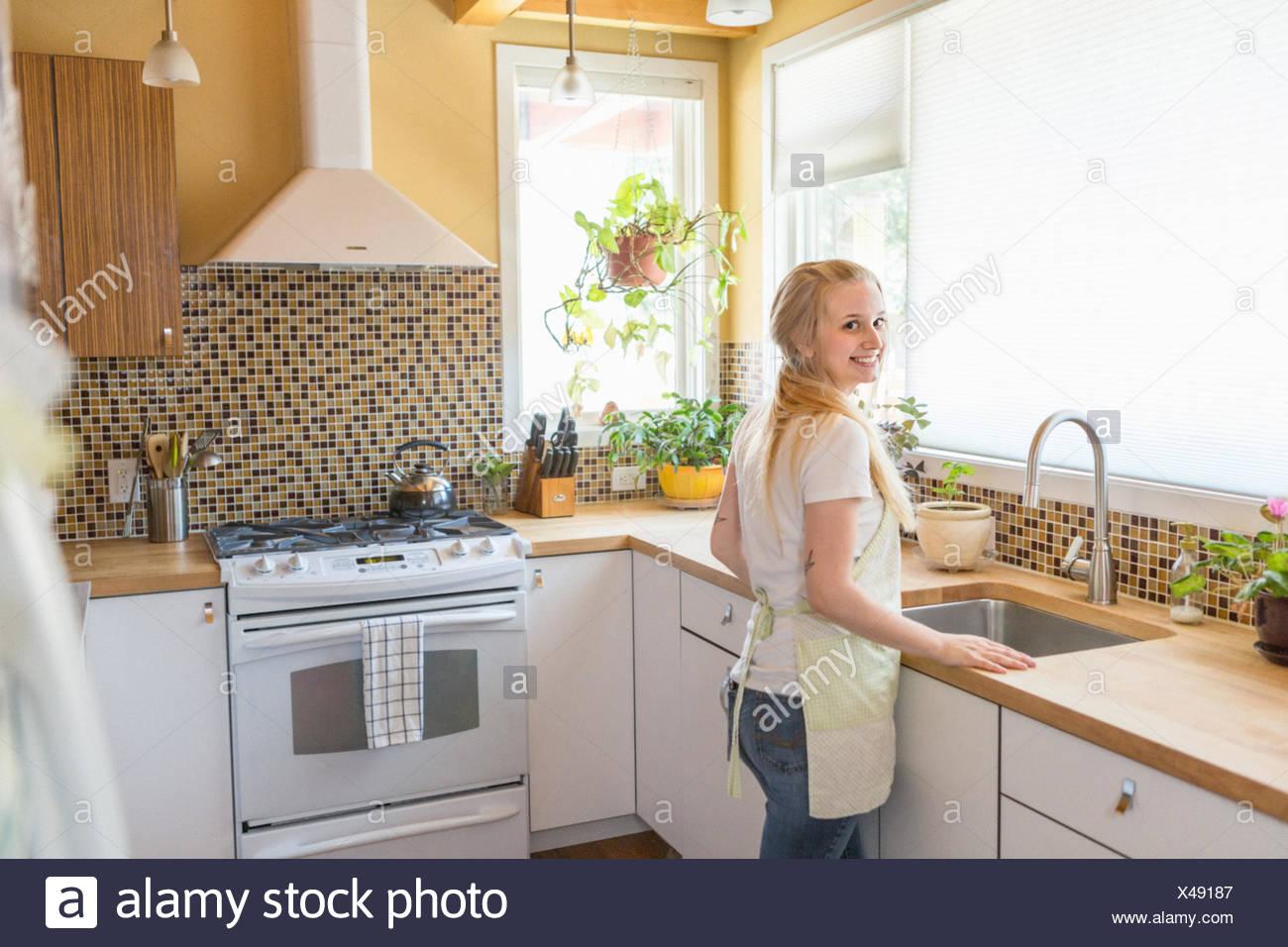 Giovane donna cucina pulizia con verde di prodotti per la ...