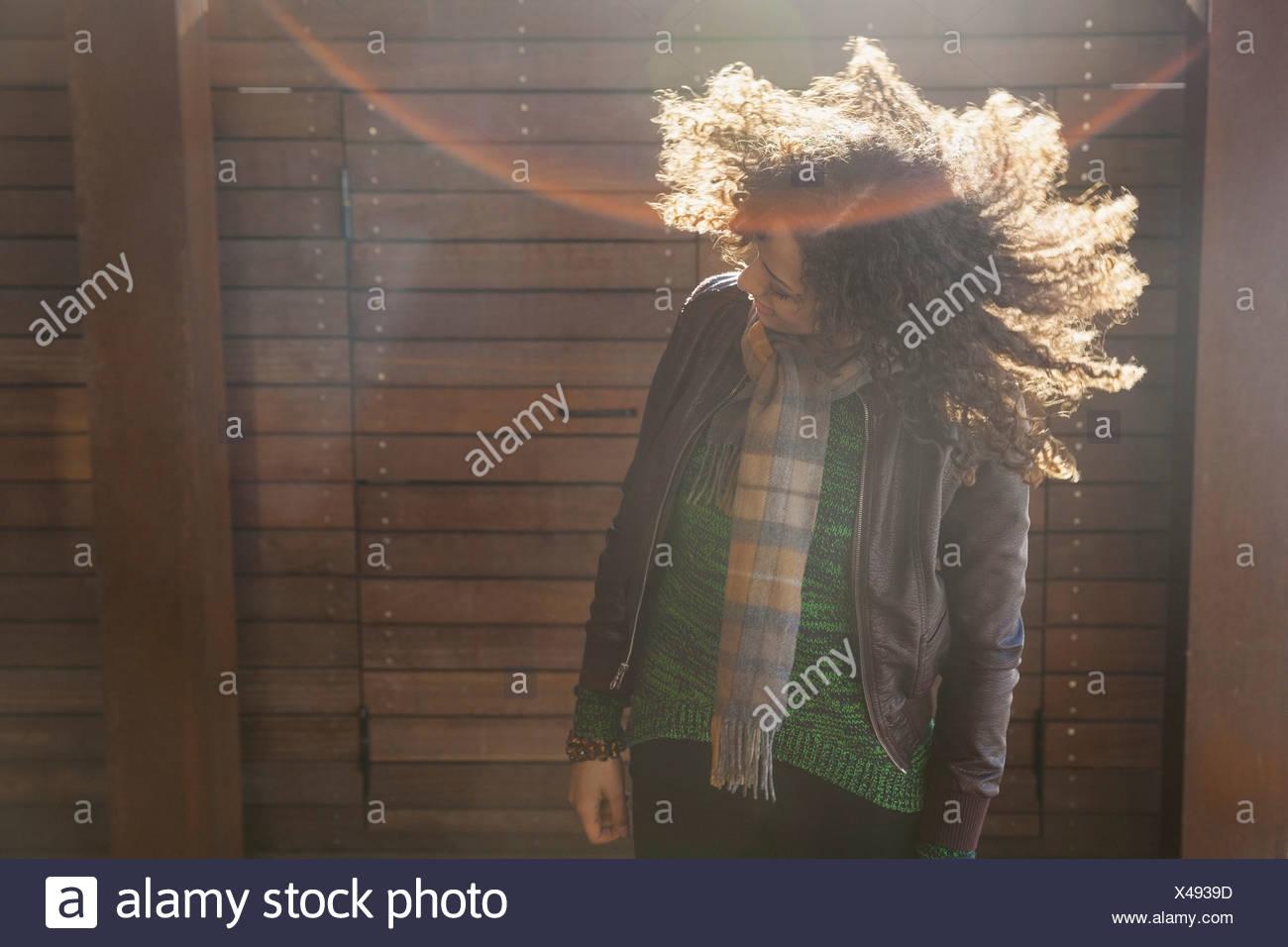 Donna in piedi all'aperto scuotendo i suoi capelli Immagini Stock