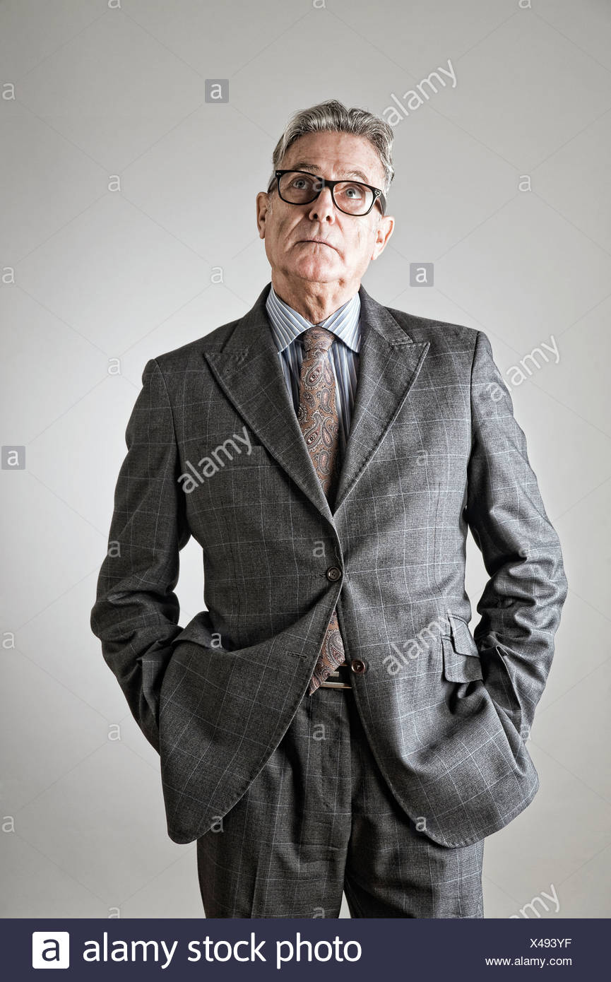 Senior uomo con le mani nelle tasche, guardando verso l'alto Immagini Stock