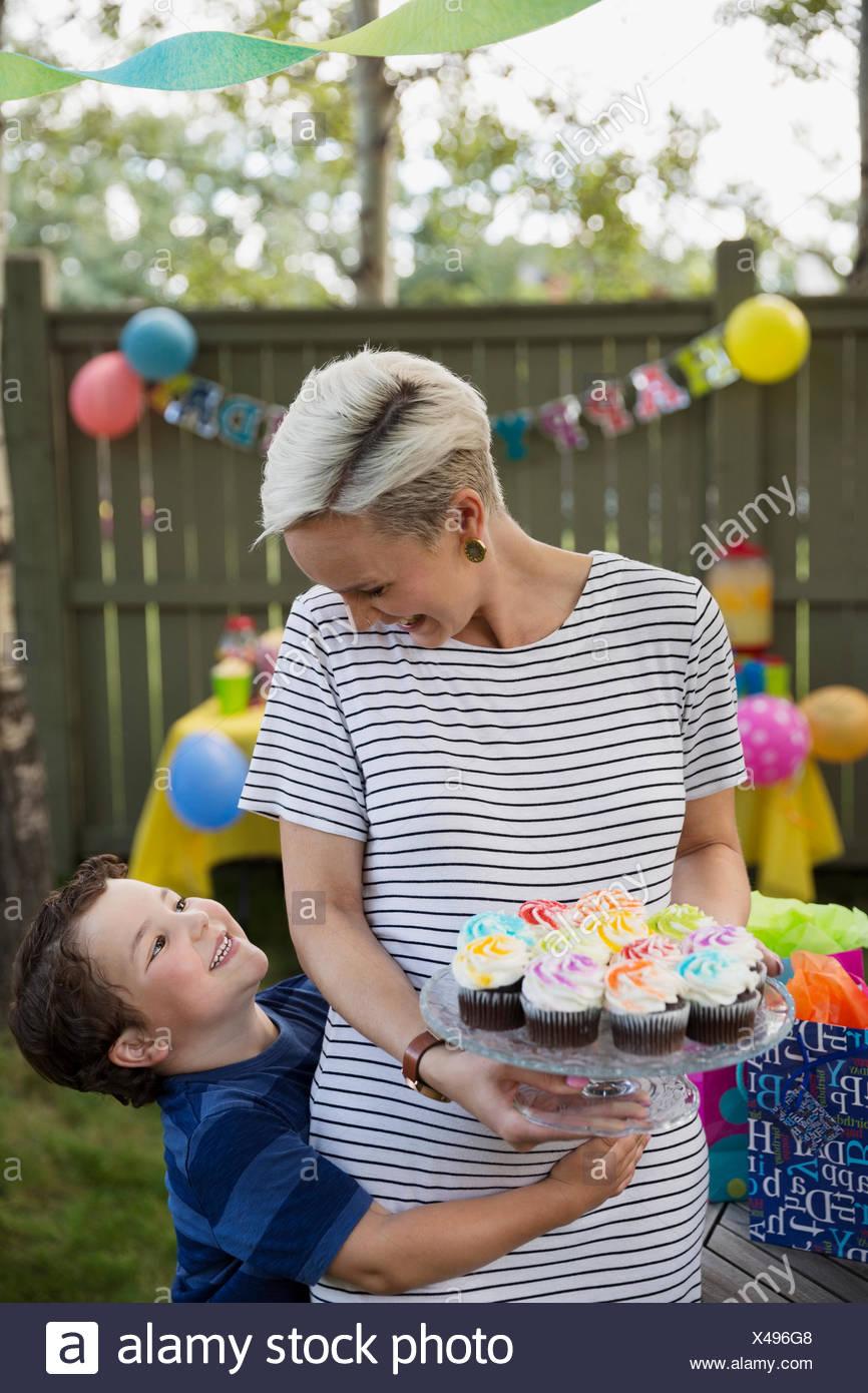 Figlio abbracciando la madre holding tortine su torta stand Immagini Stock