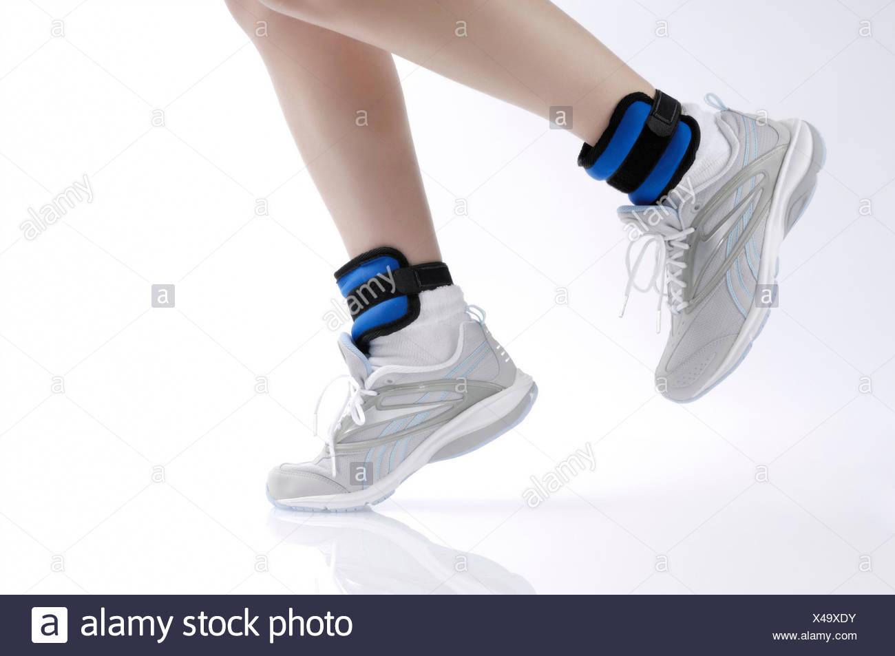 Donna jogging indossando i pesi della caviglia, dettaglio Immagini Stock