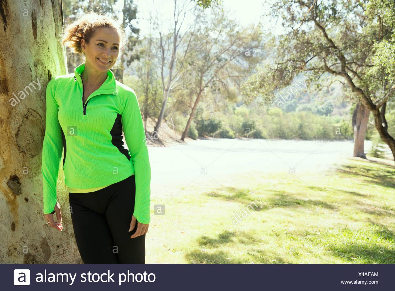 Ritratto di femmina matura runner appoggiato contro il tronco di albero in posizione di parcheggio Immagini Stock