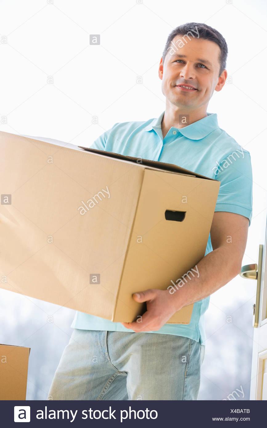 Uomo che guarda lontano mentre si trasporta la scatola di cartone mentre entrando in casa nuova Immagini Stock