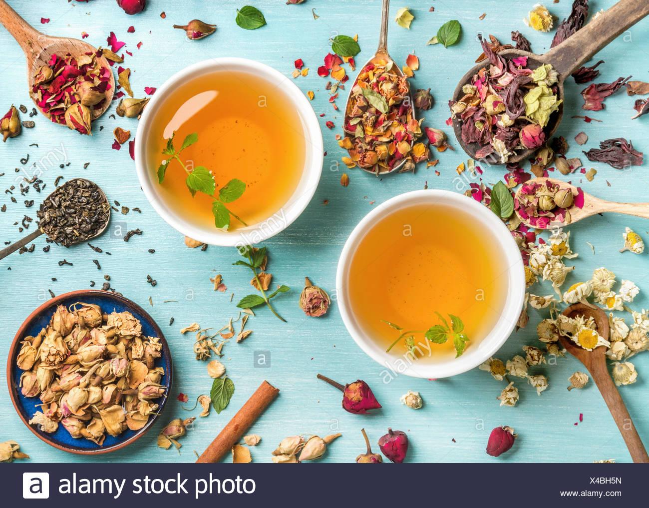 Due tazze di sano tè alle erbe con la menta, cannella, essiccato rose e fiori di camomilla in cucchiai su sfondo blu, vista dall'alto Immagini Stock