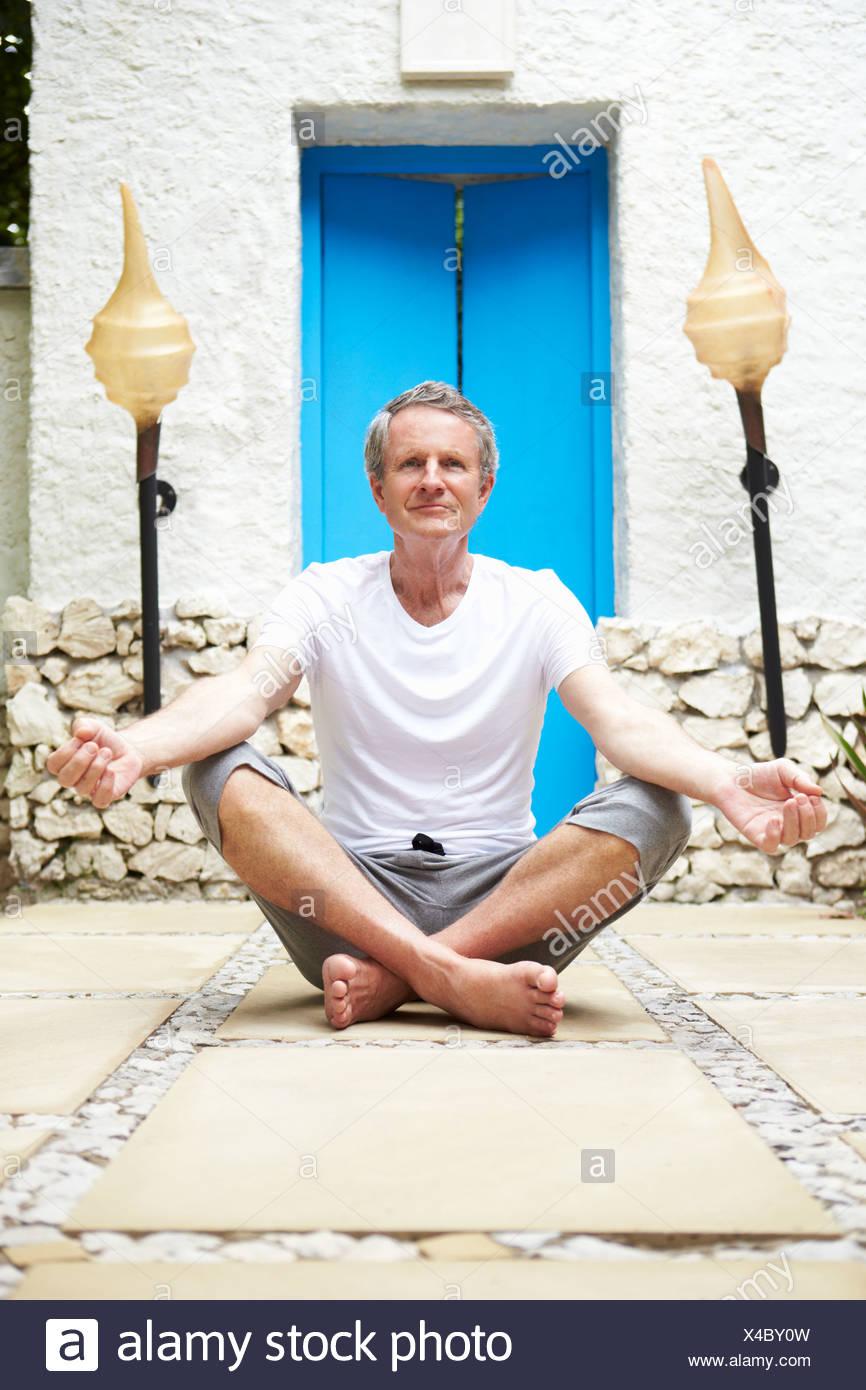 Senior uomo meditando all'aperto a Health Spa Immagini Stock