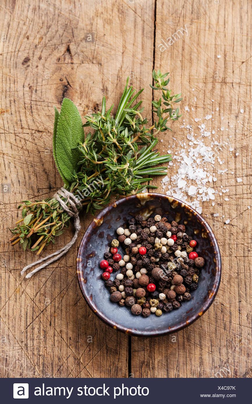 Peperoni multicolore di piselli e di erbe aromatiche su sfondo di legno Immagini Stock