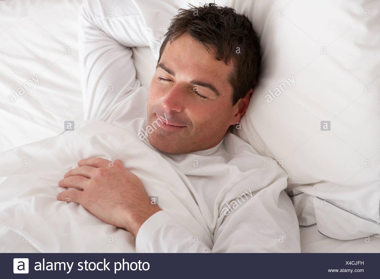Uomo dorme tranquillamente nel letto Immagini Stock