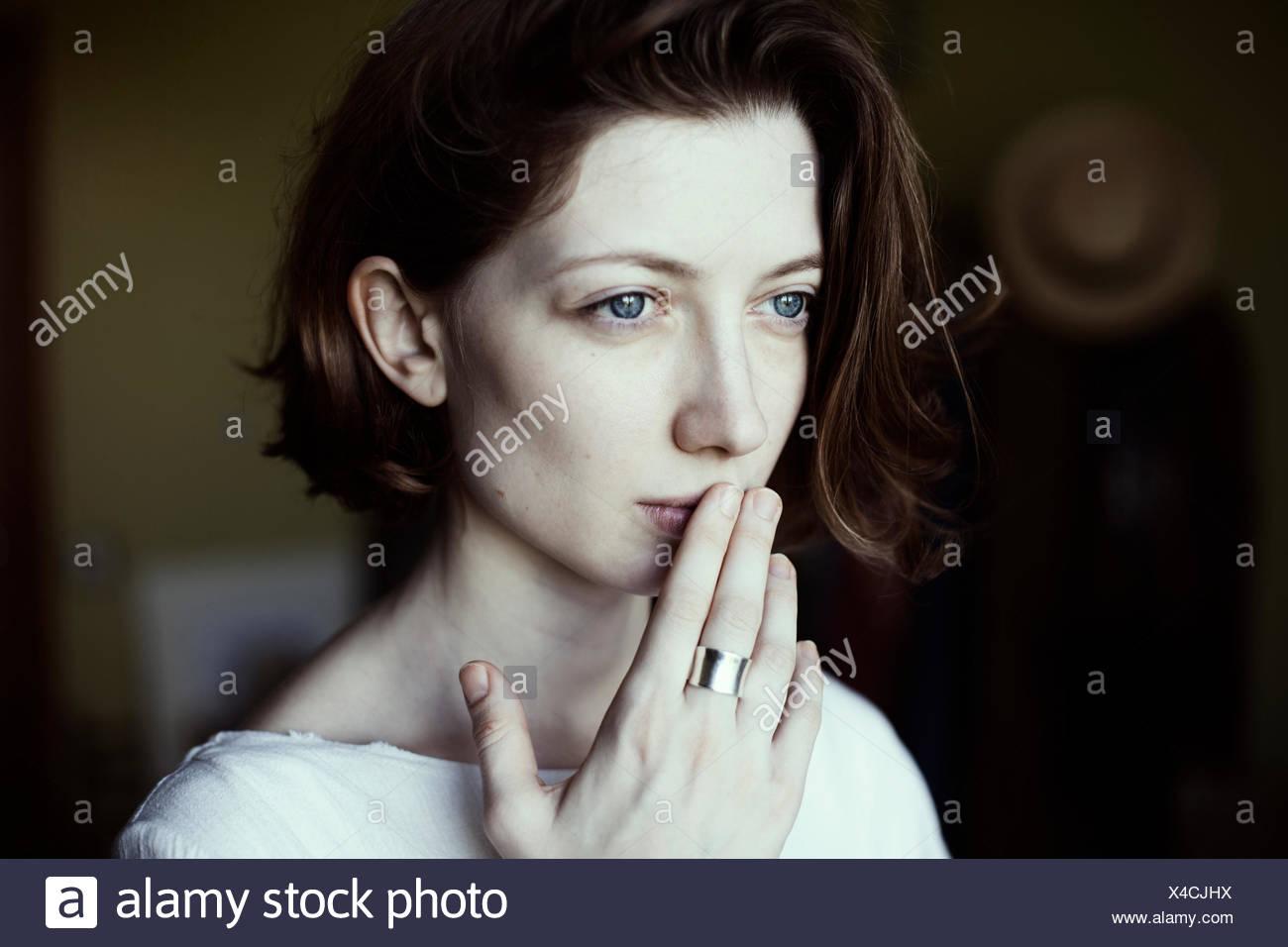 Ritratto di una donna tenendo la mano alla bocca Immagini Stock