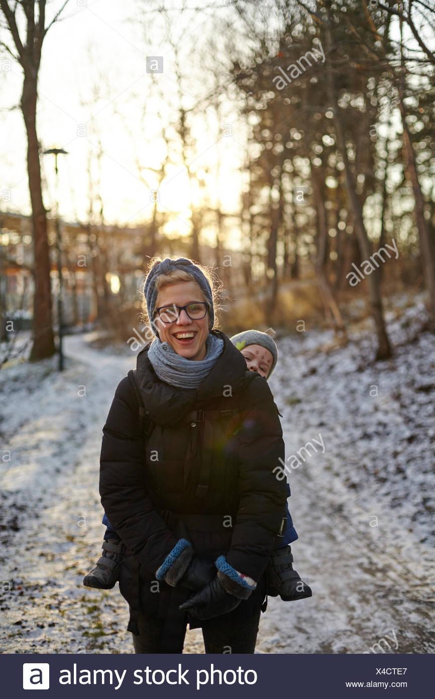 La Svezia sodermanland, Stoccolma johanneshov, hammarbyhojden, ridendo metà donna adulta che trasportano figlio (2-3) Immagini Stock