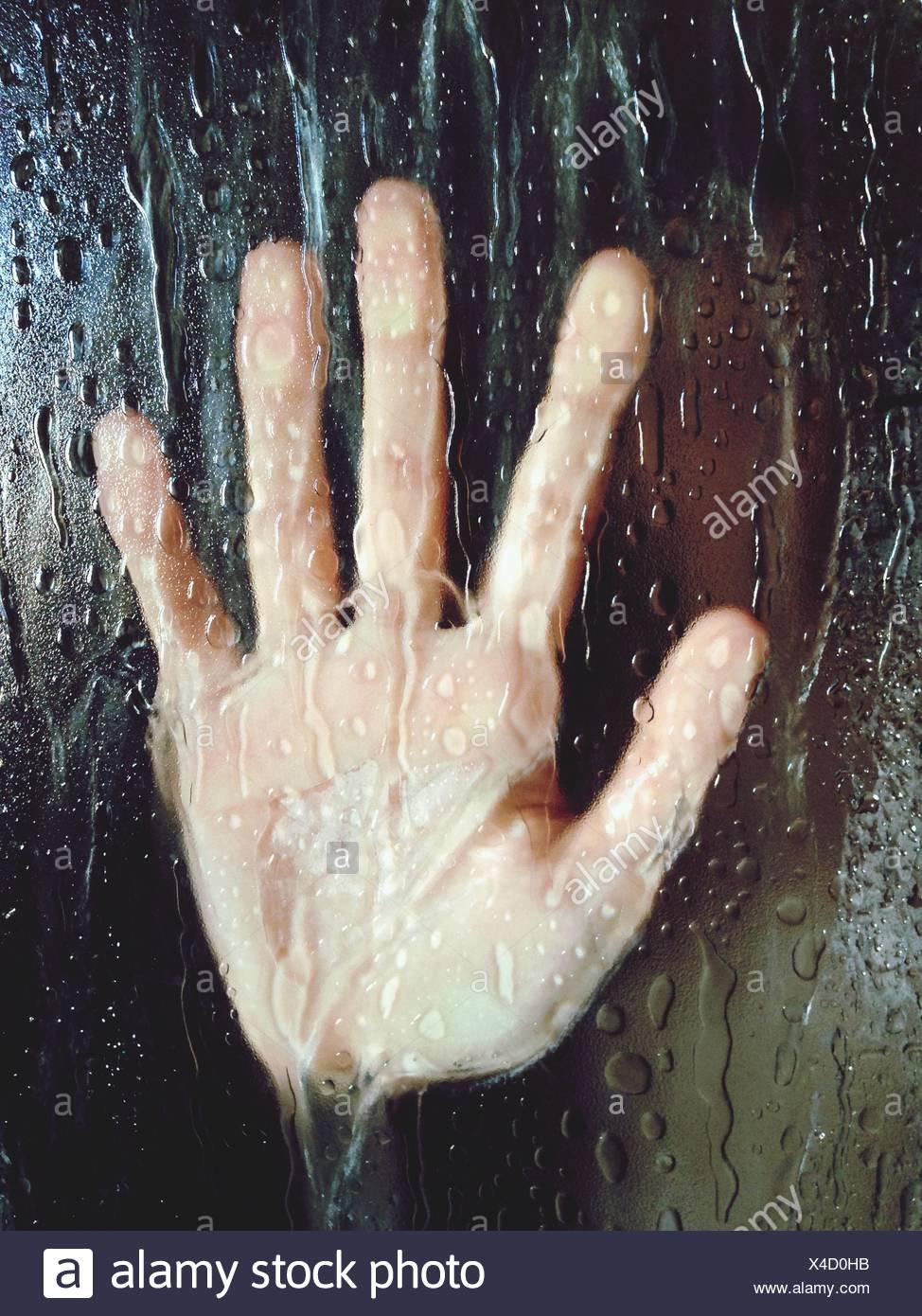 In primo piano della mano sul vetro bagnato Immagini Stock