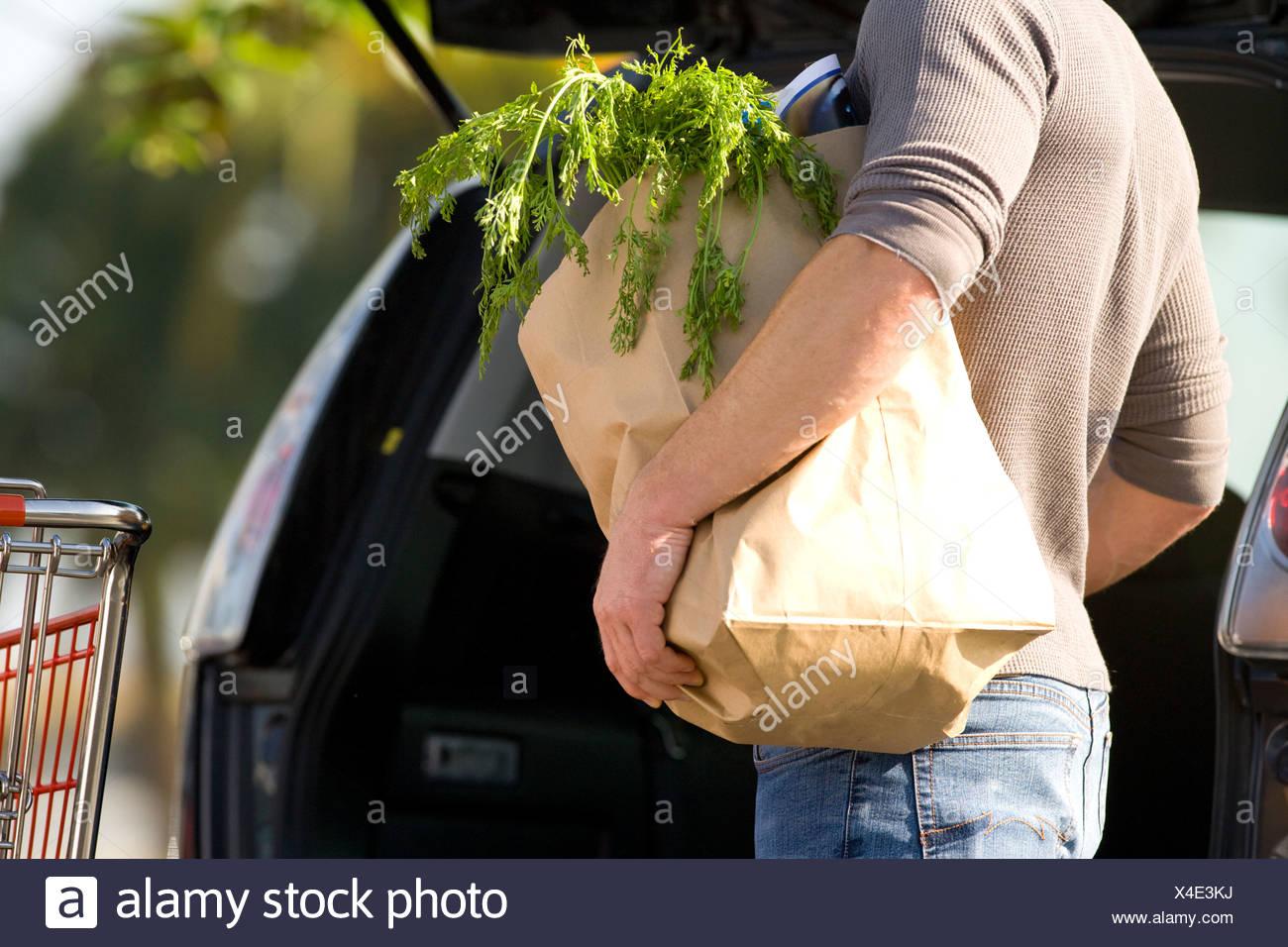 L'uomo il caricamento di generi alimentari nella parte posteriore della macchina Immagini Stock