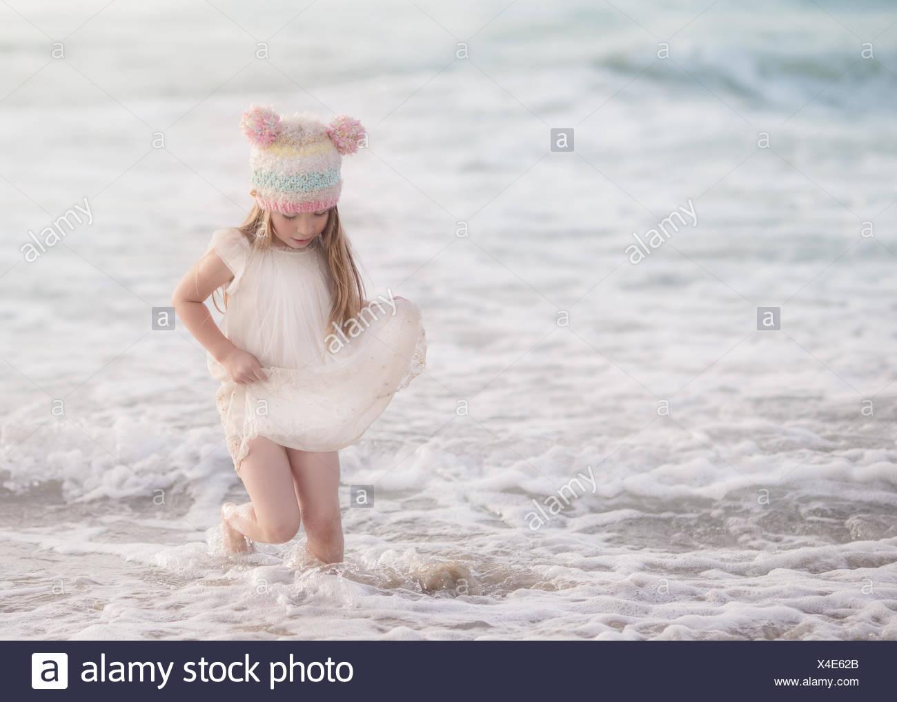 Ragazza in un abito a piedi nell'oceano Immagini Stock