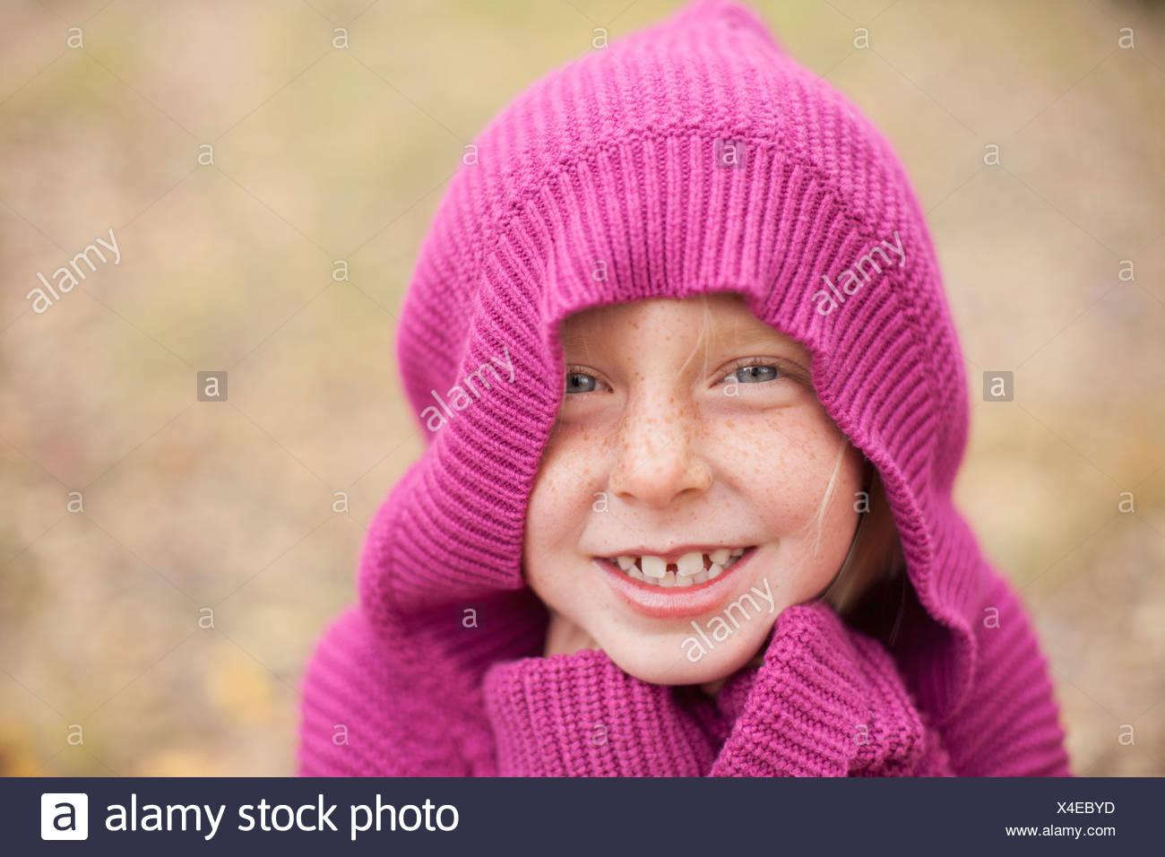 Una ragazza in un magenta felpa con cappuccio, con la cappa che copre la sua testa Immagini Stock