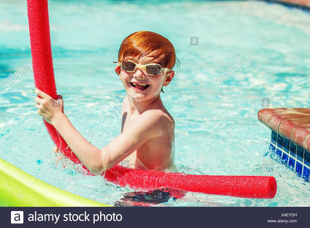 Giovane ragazzo (6-7) a giocare in piscina Immagini Stock