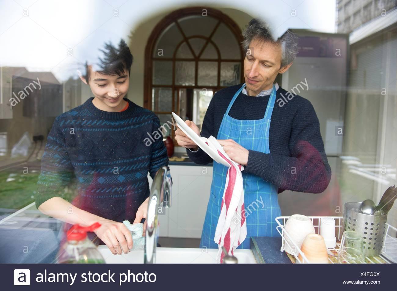 Vista attraverso la finestra del ragazzo adolescente e padre lavaggio fino in cucina Immagini Stock