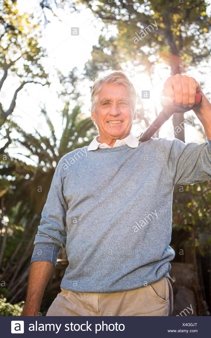 Ritratto di felice giardiniere che sostiene la pala sulla spalla al giardino Immagini Stock