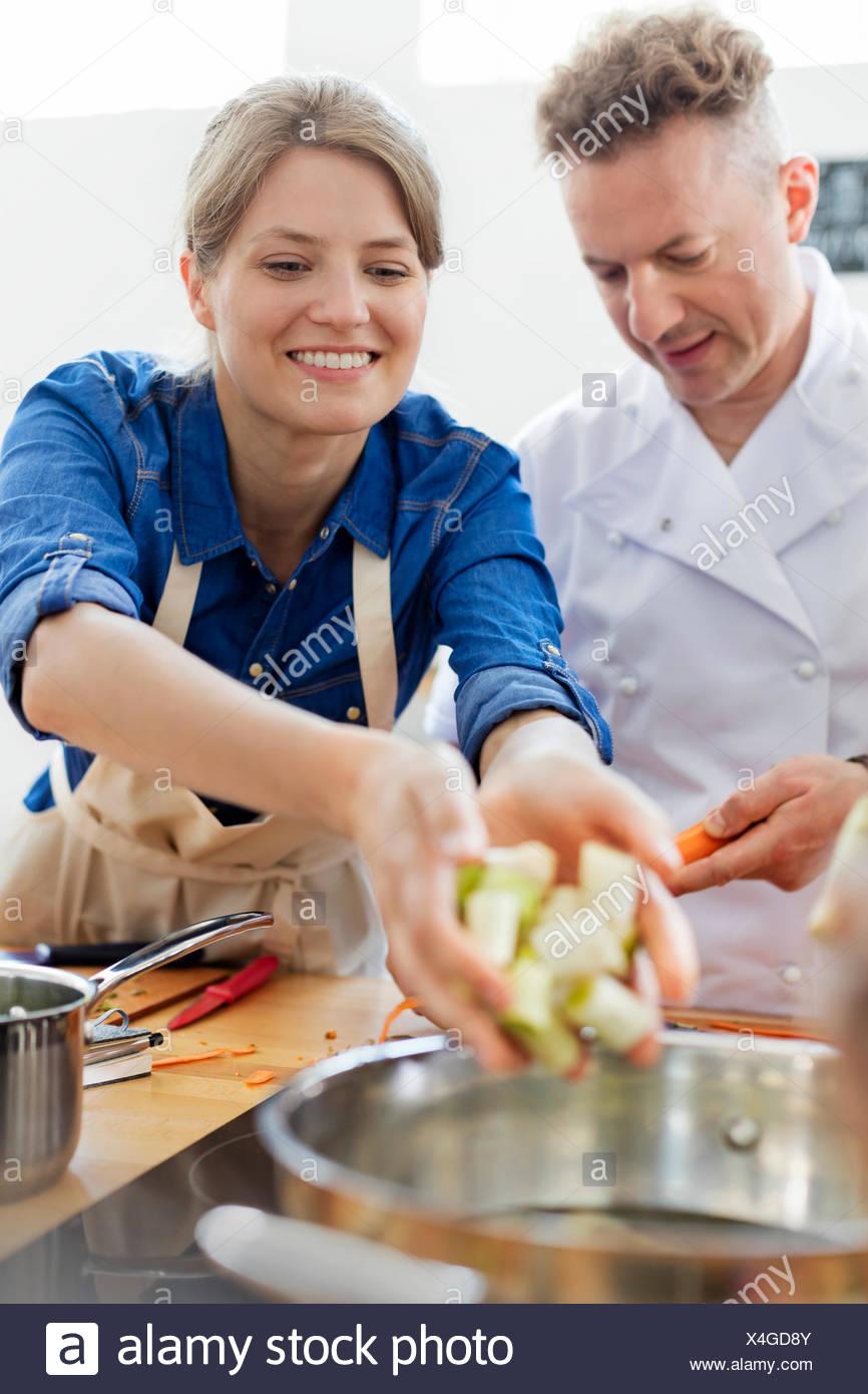 Donna mettere il cibo nella pentola in cottura cucina di classe Foto ...
