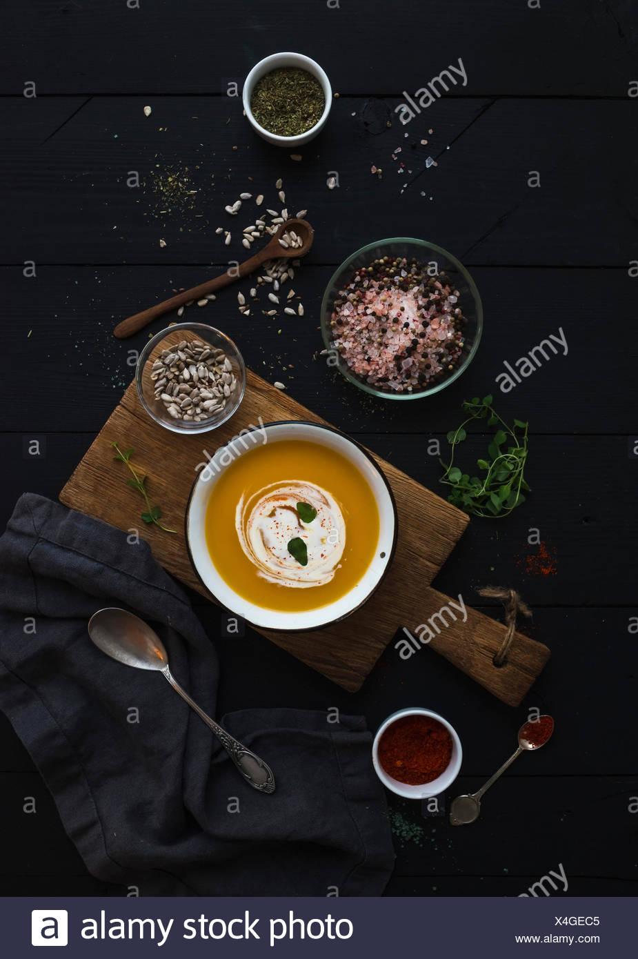 Zuppa di zucca con panna, semi e spezie in stile rustico recipiente di metallo sulla tavola di legno su grunge sfondo nero. Vista superiore Immagini Stock