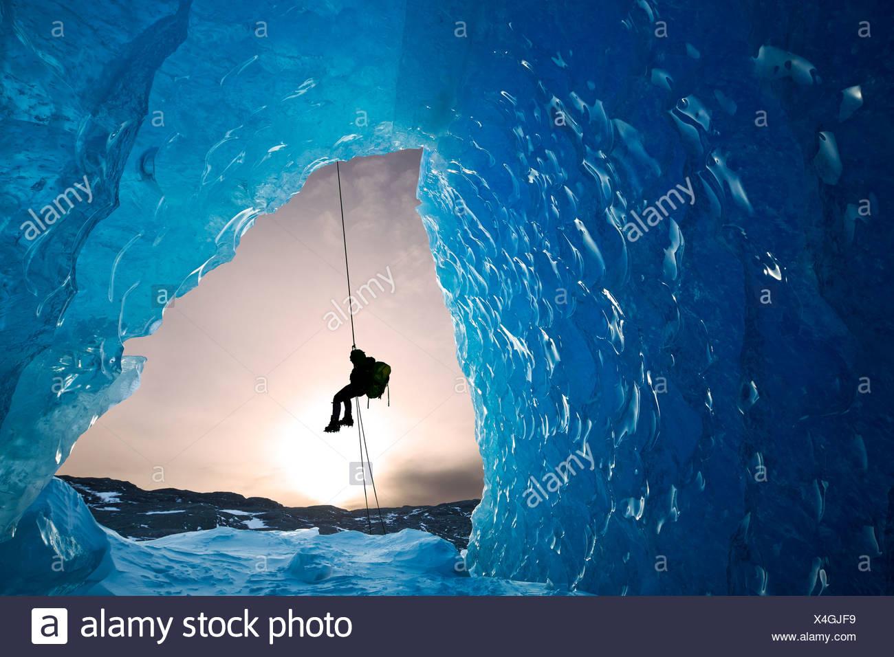 Composito: vista dall'interno di una caverna di ghiaccio di un iceberg come un alpinista rappels giù, Mendenhall Glacier, Alaska Immagini Stock