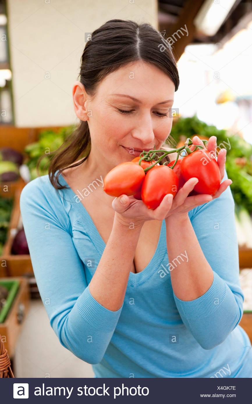 Donna prendendo odore al pomodoro fresco Immagini Stock