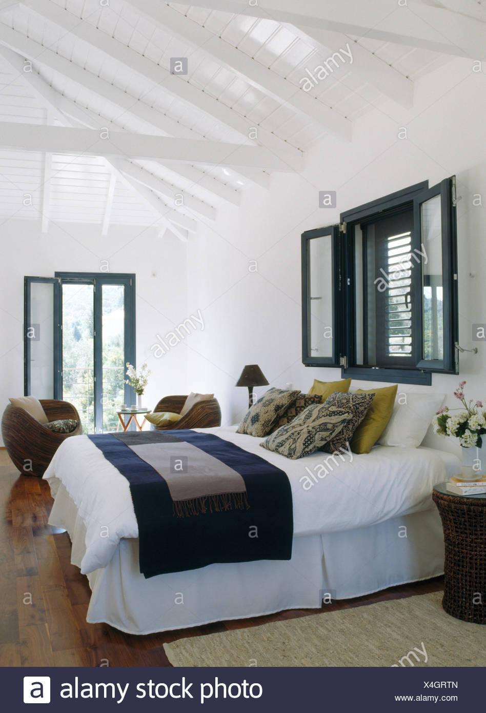 Finestra sopra il letto con biancheria bianca e blu buttare in ...