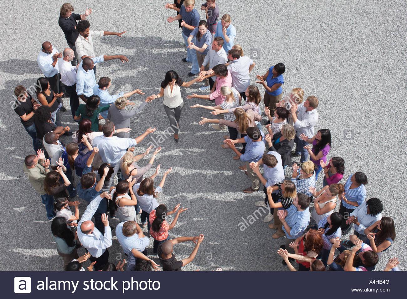 Donna che cammina tra due gruppi di persone, persone che applaudono Immagini Stock