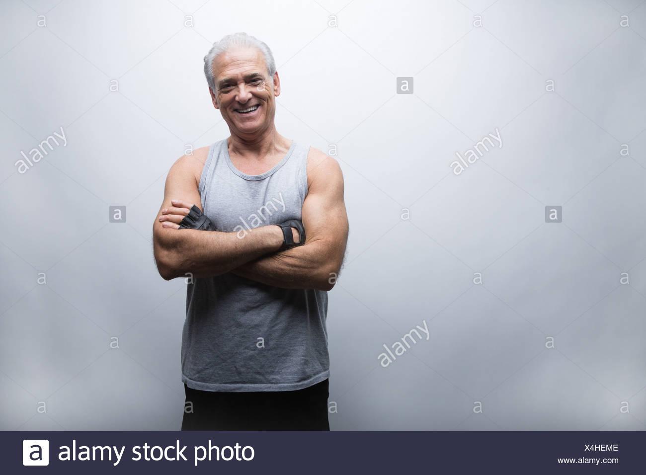 Senior uomo in abbigliamento sportivo con le braccia incrociate, ritratto Immagini Stock