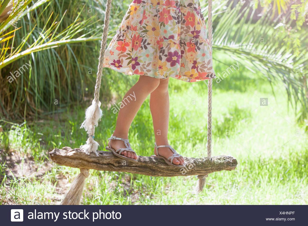 Vita scende ritagliato shot della ragazza in piedi su albero oscillante nel giardino Immagini Stock