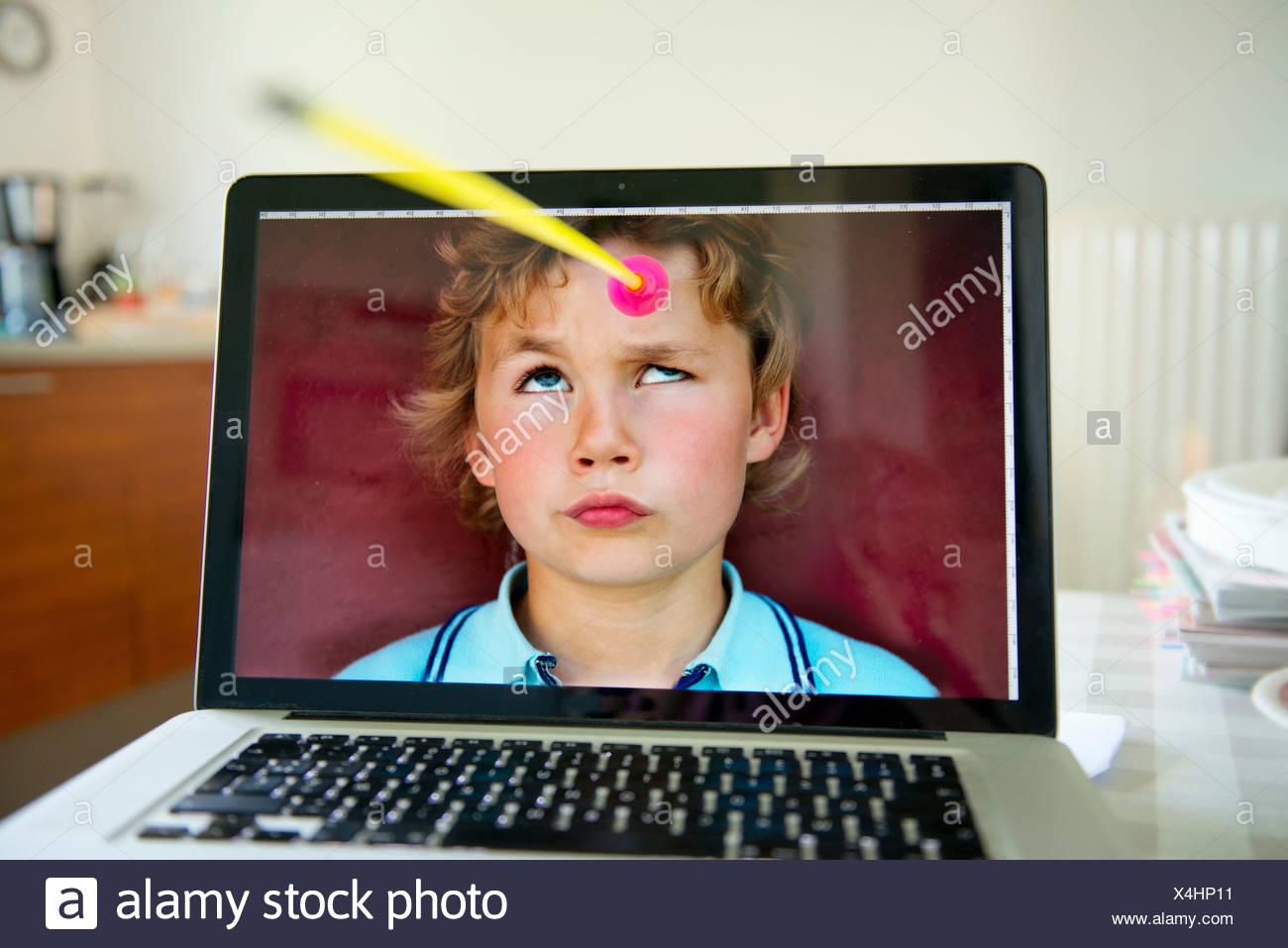 Ragazzo che guarda verso l'alto dallo schermo del computer portatile a freccia giocattolo Immagini Stock