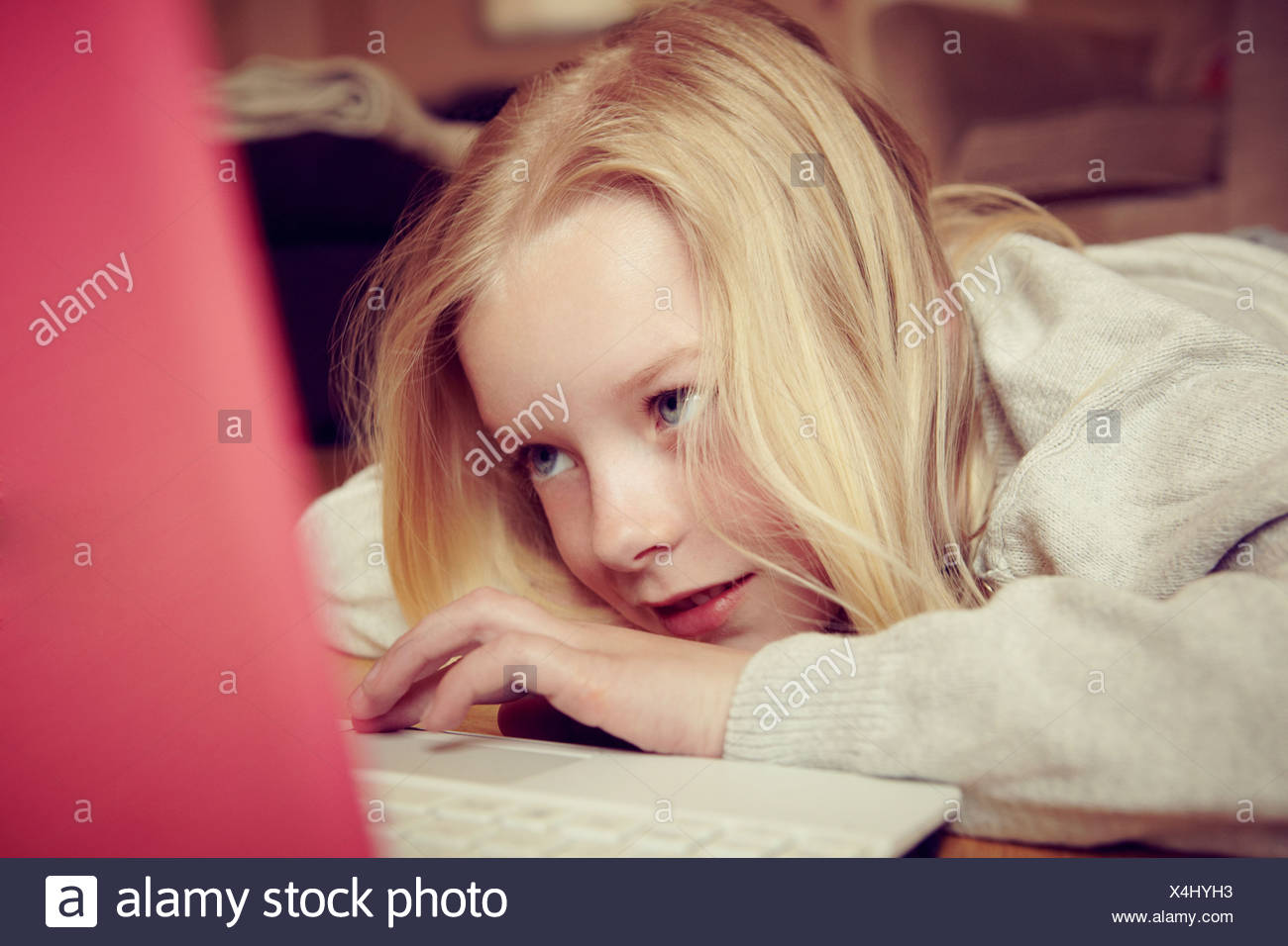 Ragazza giovane disteso sul pavimento con laptop Immagini Stock