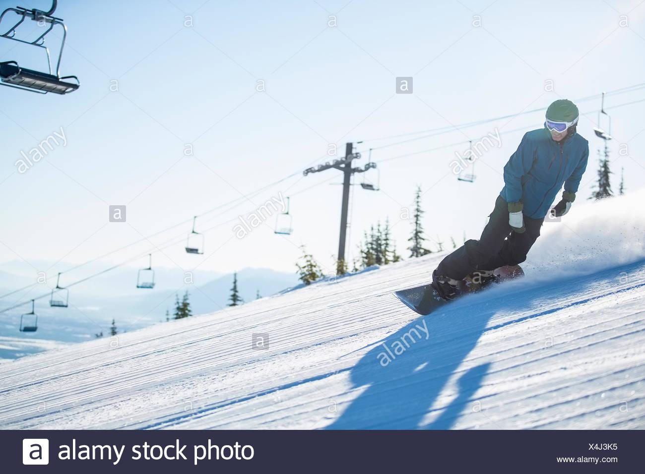 L uomo lo snowboard in discesa Immagini Stock