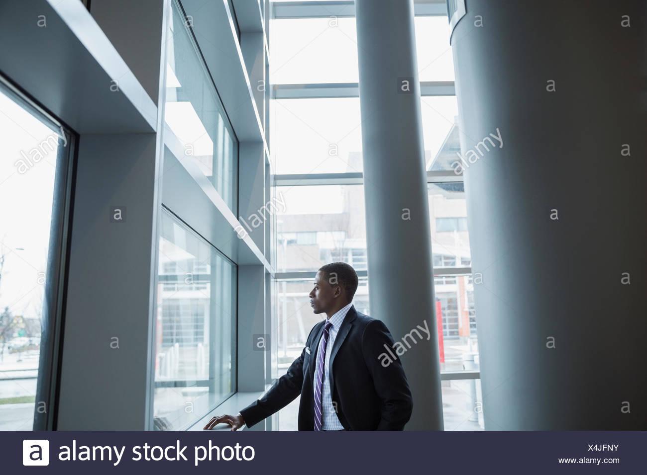 Imprenditore pensieroso a guardare fuori dalla finestra Immagini Stock