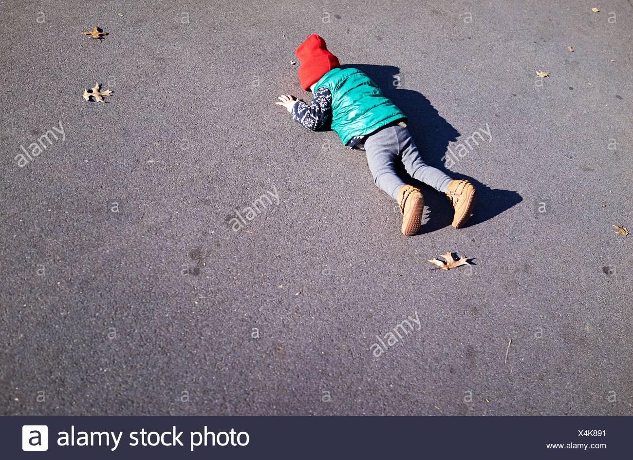 Ragazzo sdraiato a faccia in giù sulla strada Immagini Stock