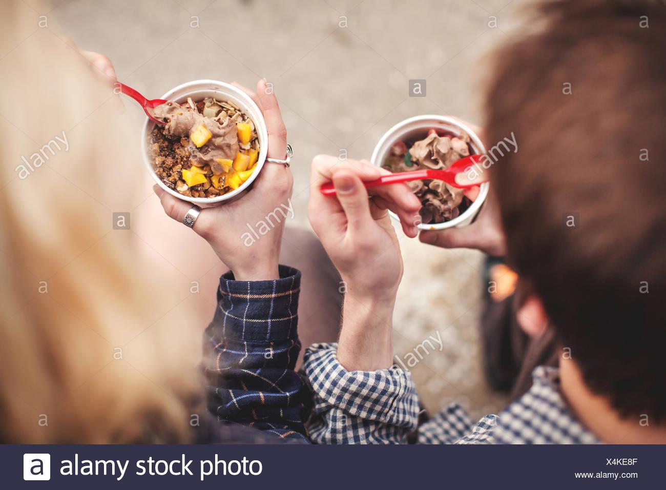 Paio mangiare vaschette di yogurt surgelato trattare Immagini Stock