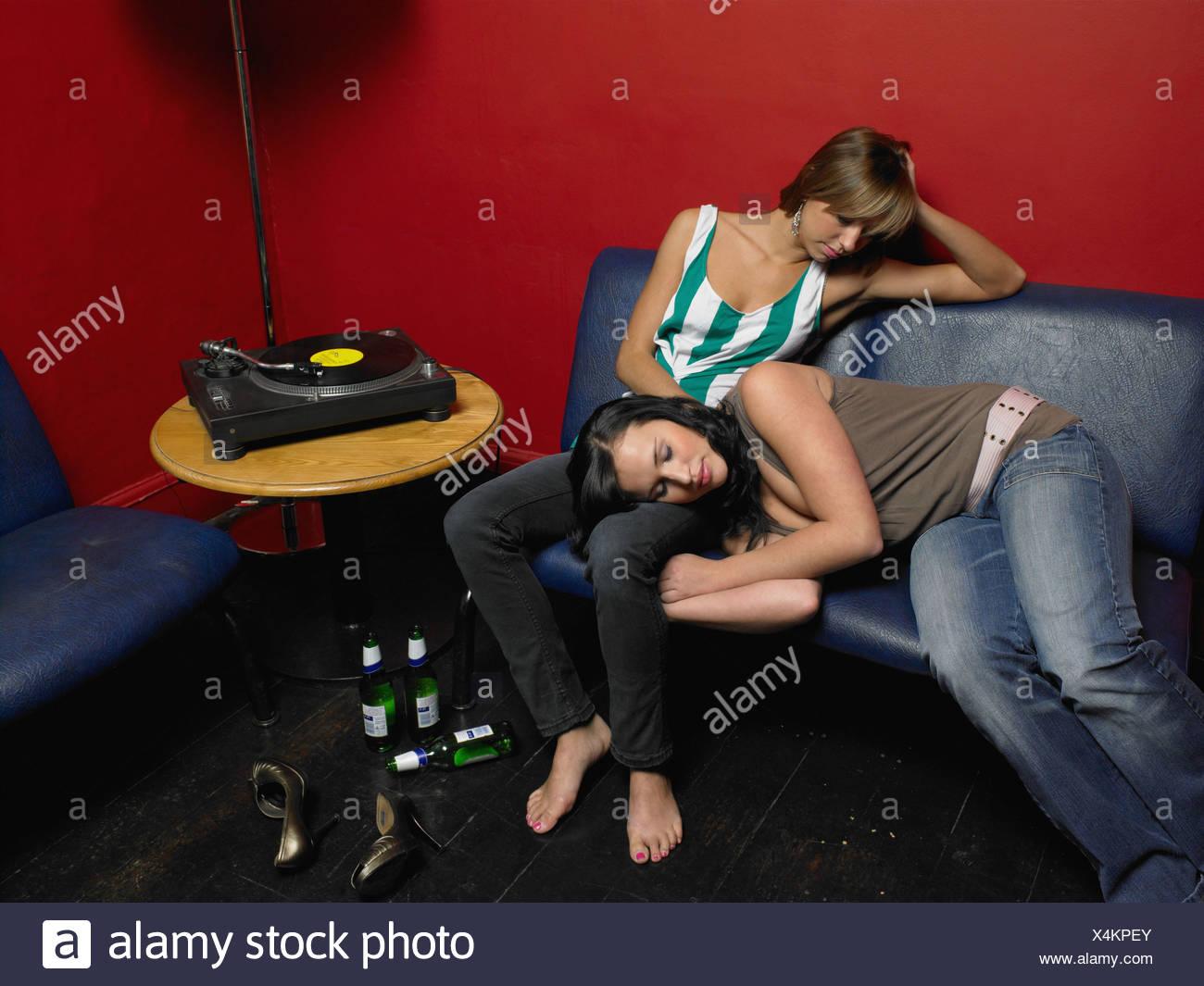 Due amici che dorme sul divano dopo una festa Immagini Stock