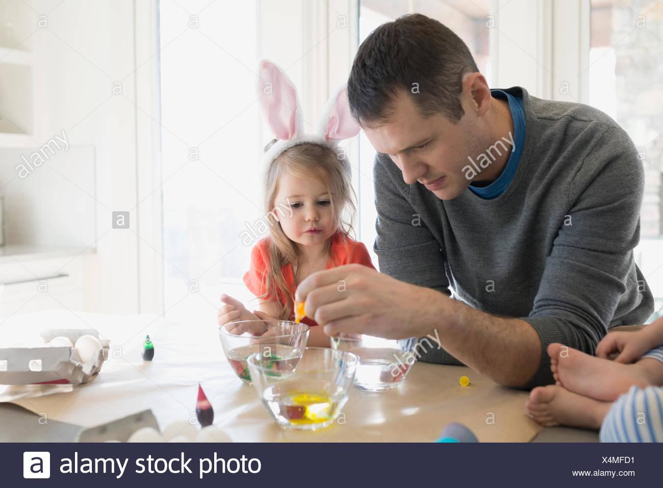 Padre e figlia preparazione colorante alimentare le uova di Pasqua Immagini Stock