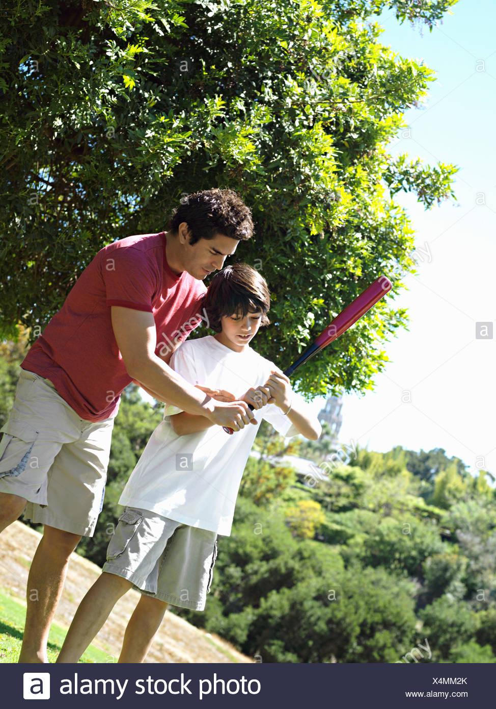 Padre figlio di insegnamento 10 12 come tenere mazza da baseball in piedi su erba in inclinazione del parco Immagini Stock