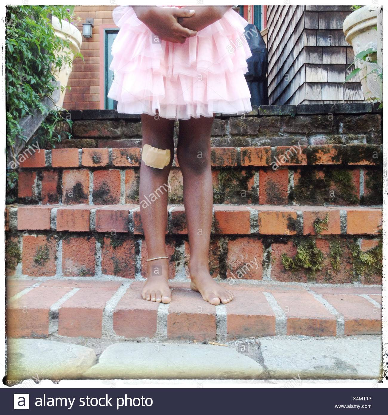 Ragazza con aiuto di banda sul suo ginocchio Immagini Stock