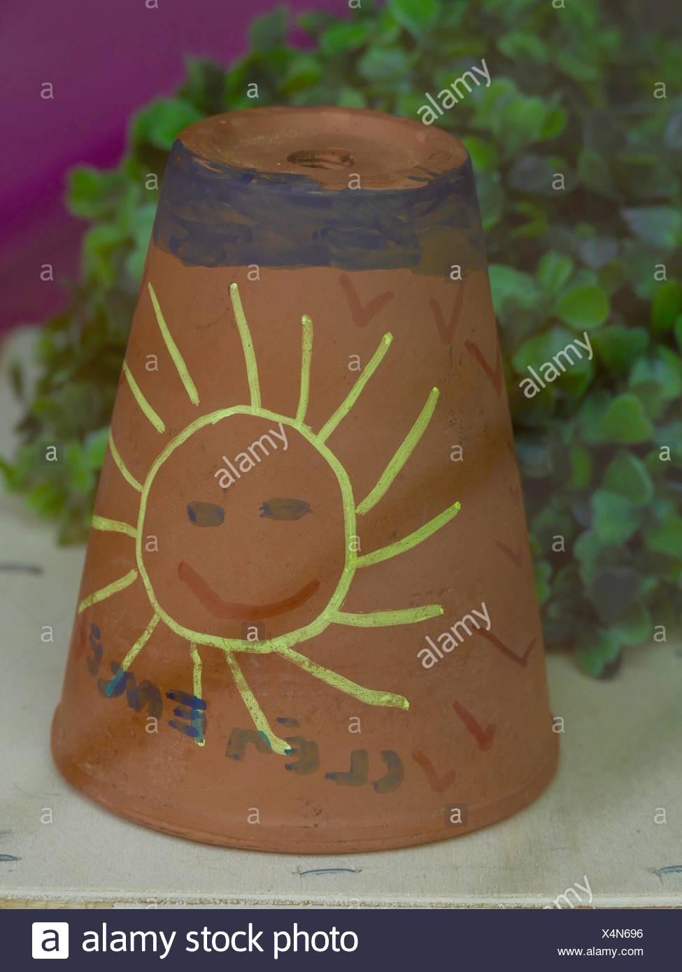Sun antropomorfo disegnato sulla pianta invertita Pot Immagini Stock