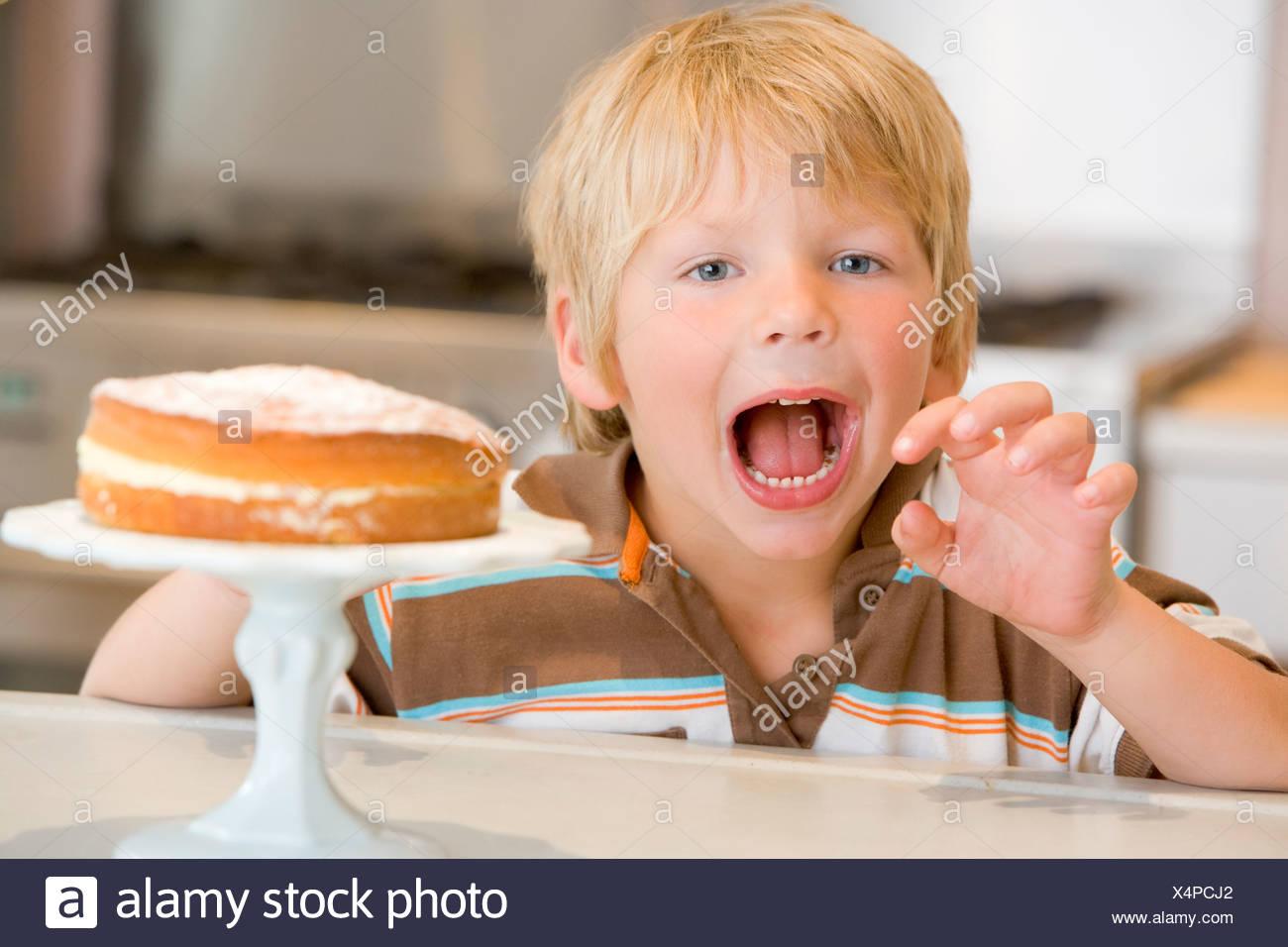 Giovane ragazzo in cucina con torta sul contatore Immagini Stock