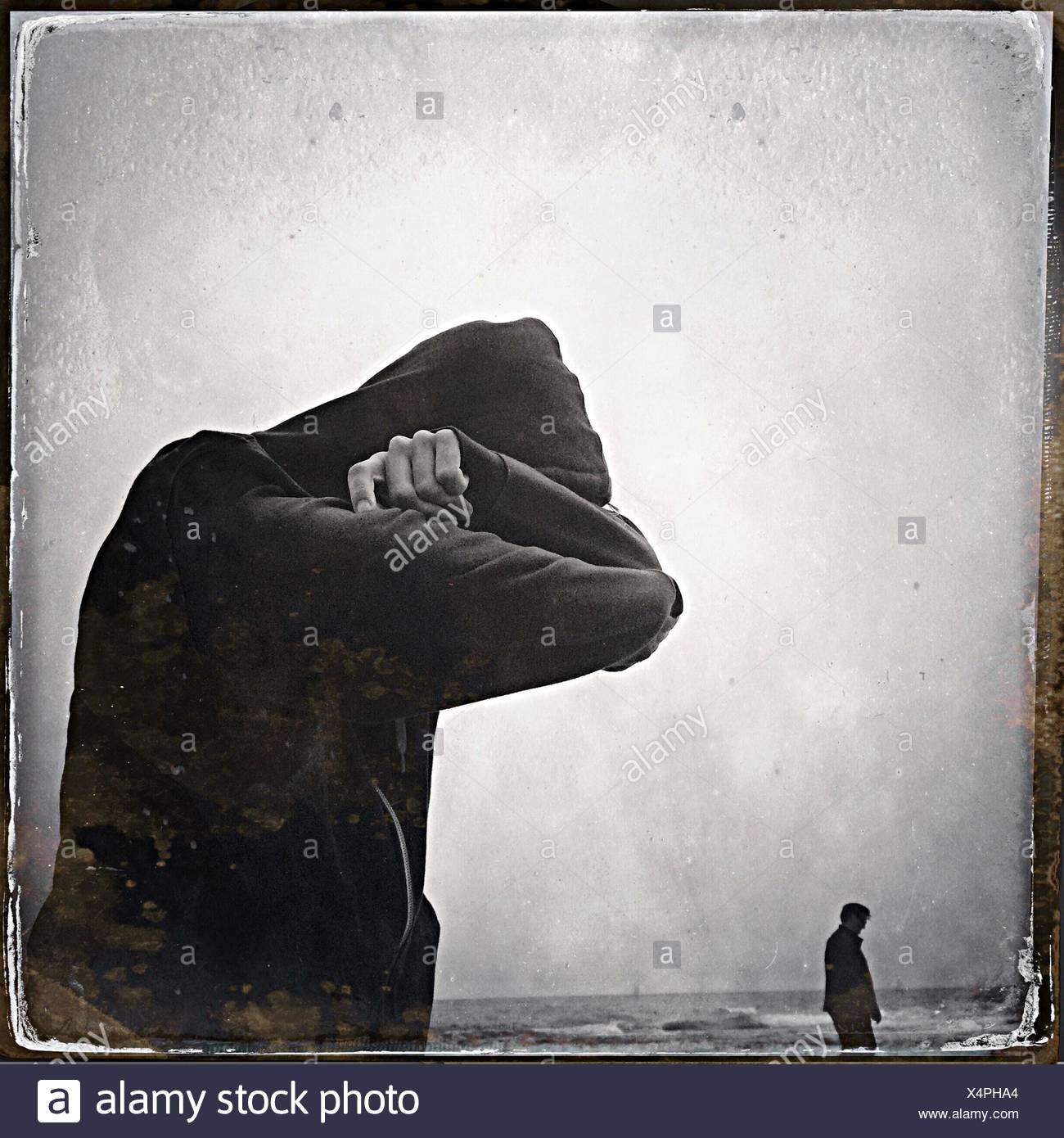 Vista laterale dell'uomo nascondendo la faccia contro il mare Immagini Stock