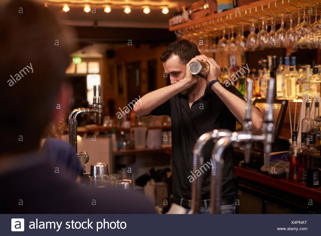 Barman rendendo cocktail nel bar utilizzando Shaker Immagini Stock