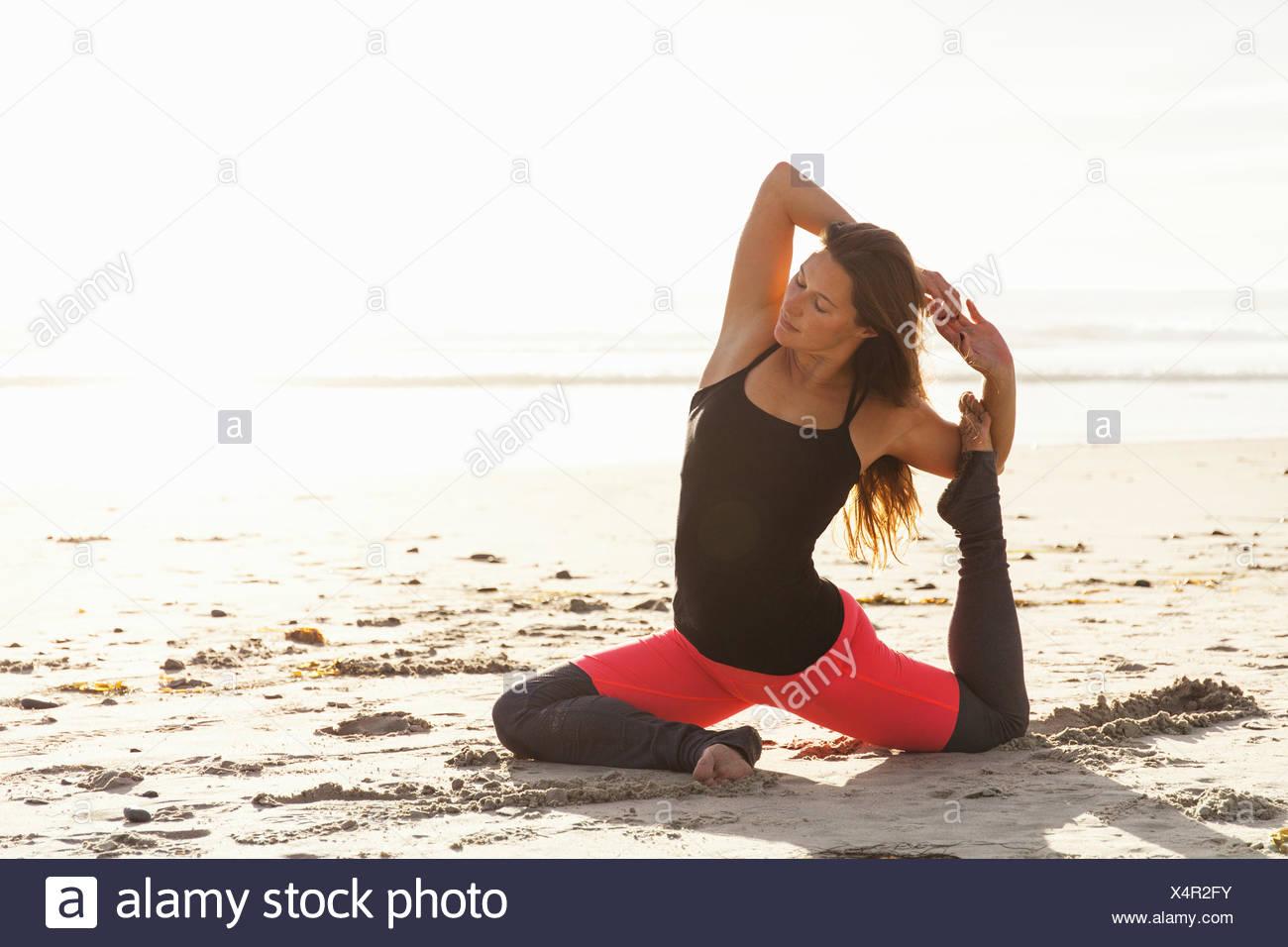 Donna in posa yoga sulla spiaggia Immagini Stock