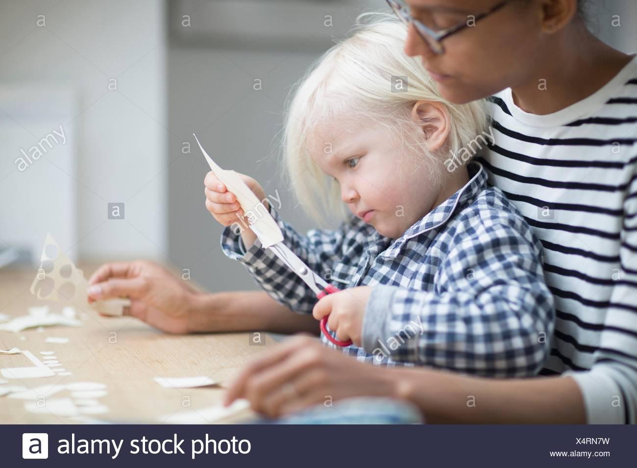 Ragazzo con le forbici per tagliare la carta con sua madre Immagini Stock