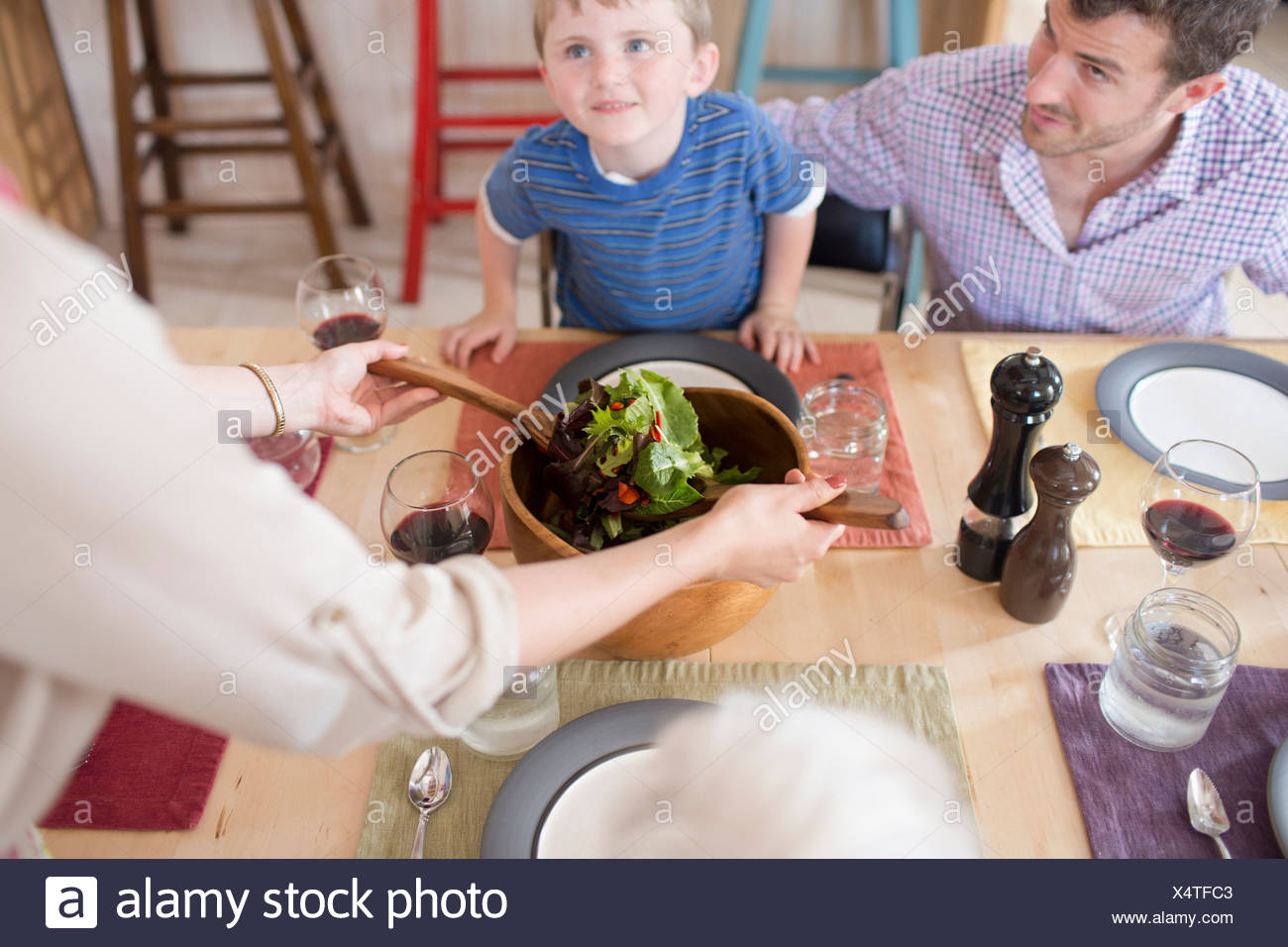 Padre e figlio guardando verso l'alto dal tavolo per la cena Immagini Stock