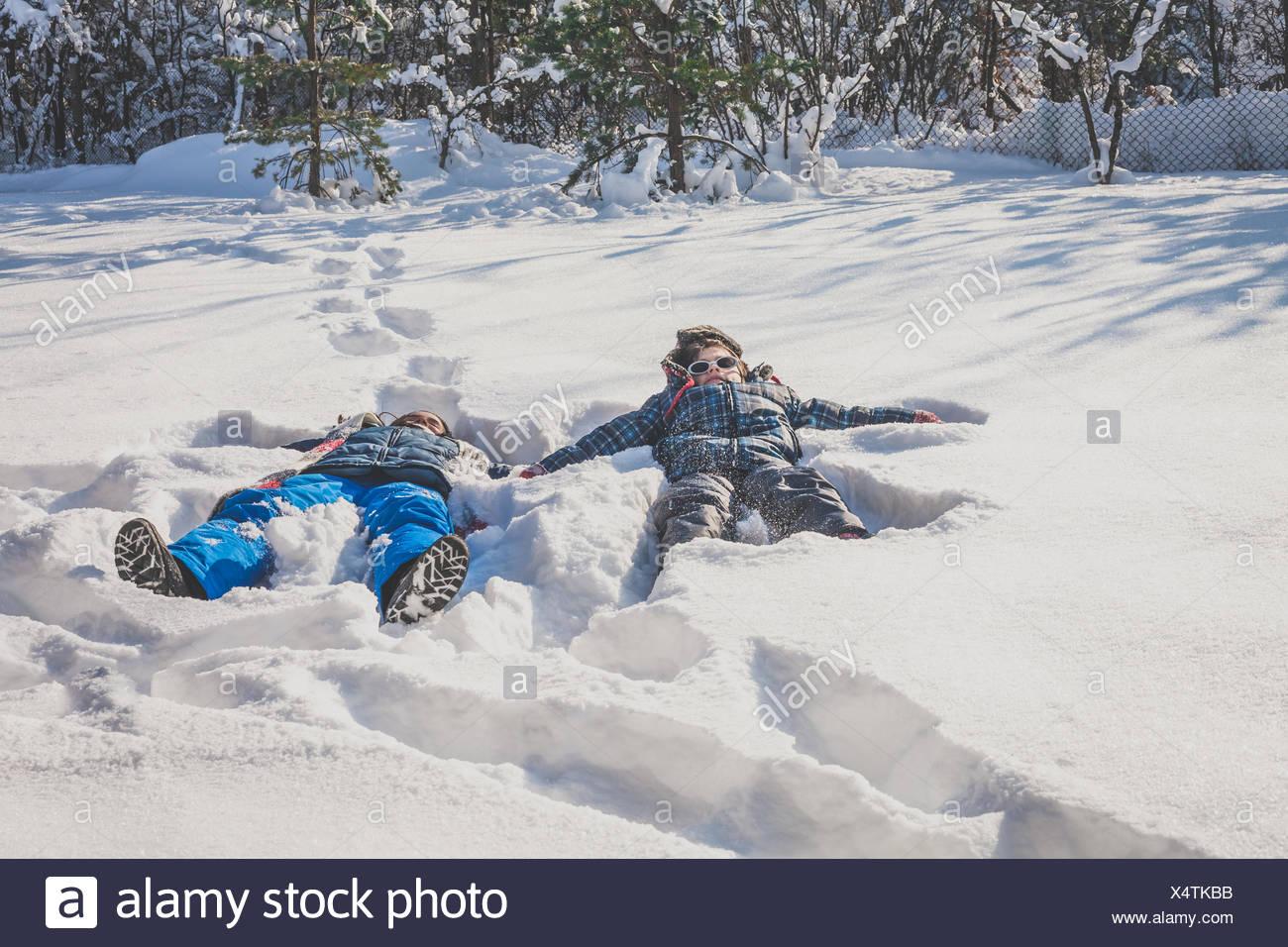 Un ragazzo e una ragazza che giace in snow making angeli di neve nella neve Immagini Stock