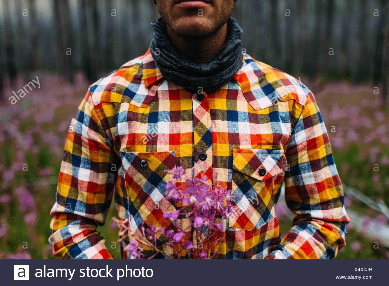 Vista ritagliata della metà uomo adulto che indossa controllato shirt holding fiori selvatici, Moraine Lake, il Parco Nazionale di Banff, Alberta Canada Immagini Stock