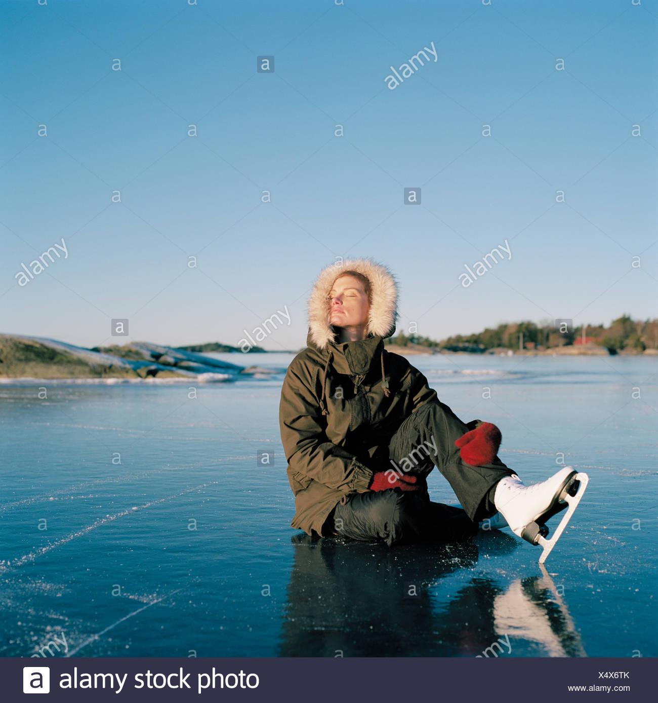 La Svezia, Uppland, Varmdo, Bjorno, metà donna adulta seduta sul lago ghiacciato Immagini Stock