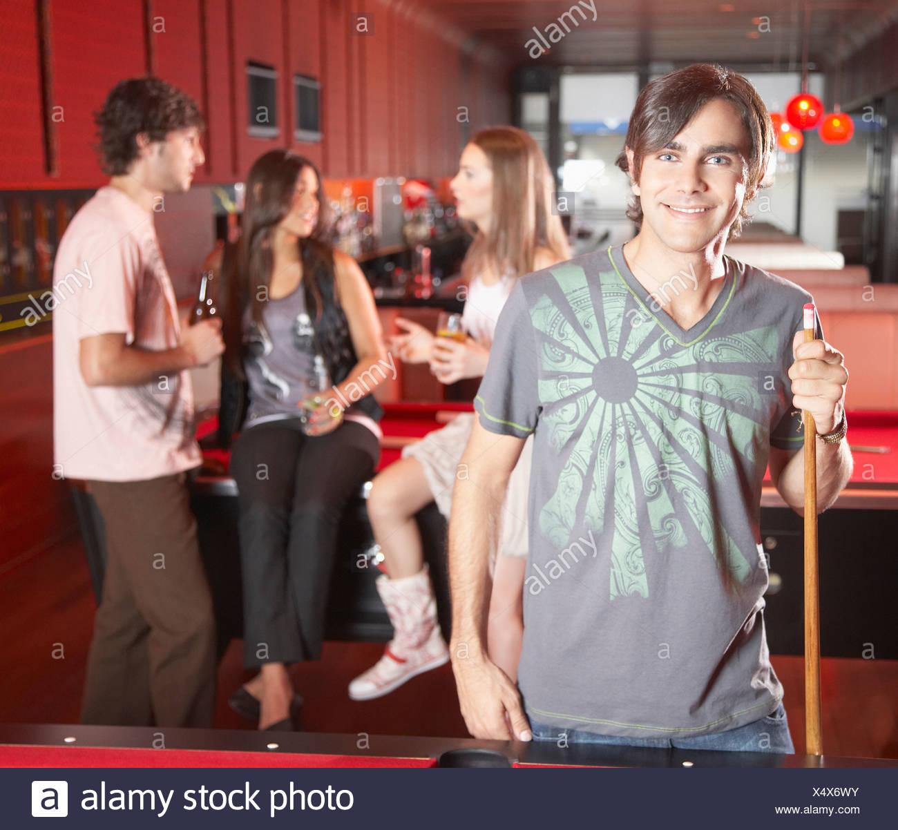 Uomo con piscina cue da tavolo da biliardo e sorridente Immagini Stock