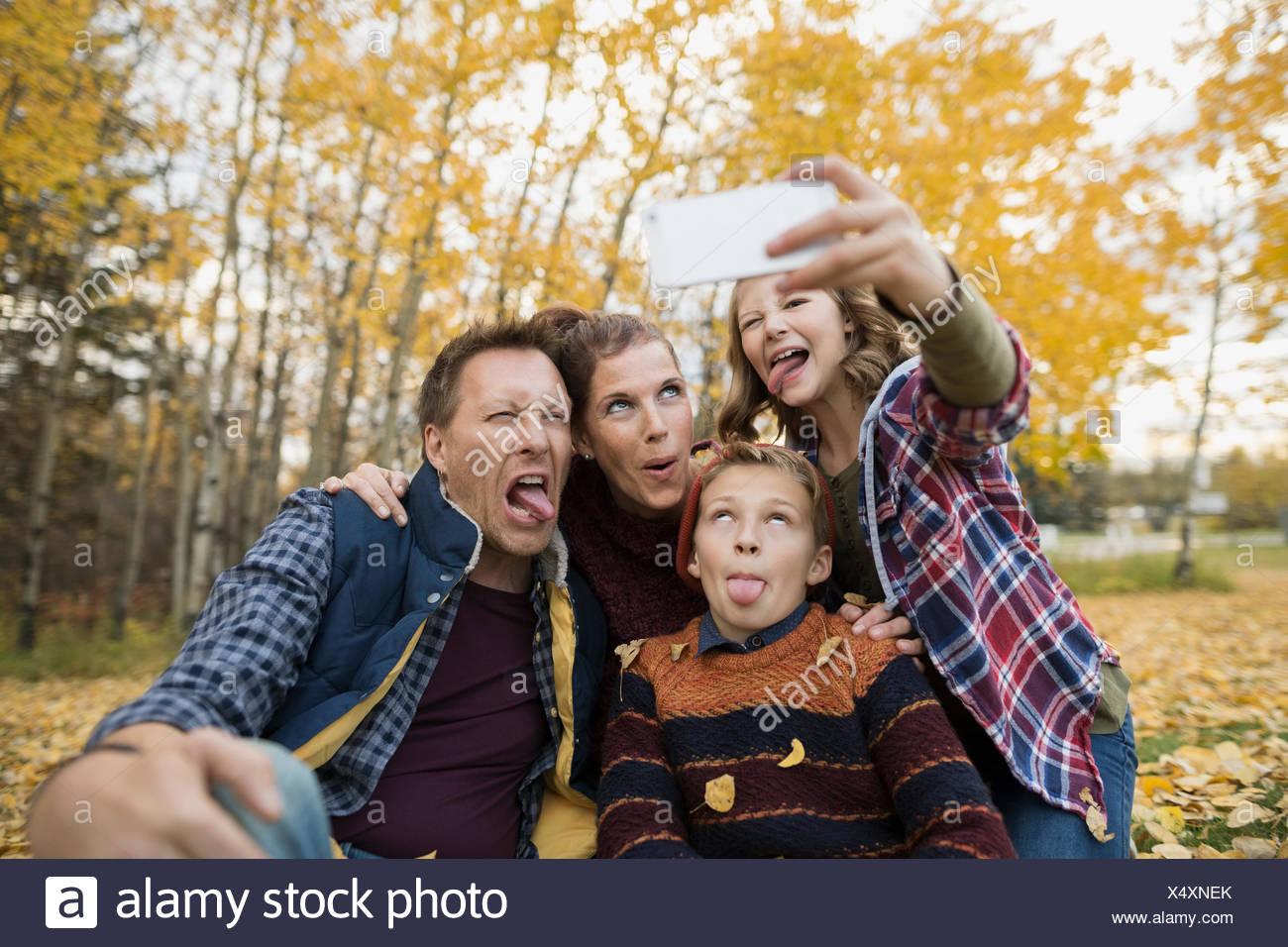 Silly famiglia tenendo selfie rendendo volti autunno park Immagini Stock